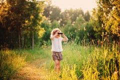 Uccelli di sorveglianza del bambino felice con binoculare nella foresta di estate Immagine Stock