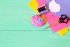 Uccello del feltro, fili e un ago, strati di feltro, perni, forbici, modelli di carta - insieme di cucito su un fondo di legno ve Immagini Stock Libere da Diritti