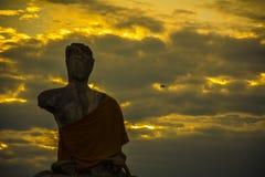 Uccello della mosca e di Buddha nel tramonto Fotografia Stock