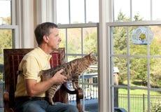 Uccello di sorveglianza del gatto sull'alimentatore Immagine Stock