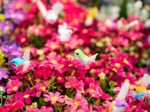 Uccello falso verde sui fiori artificiali rossi Fotografia Stock