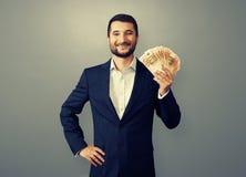 Uccessful affärsman som rymmer pappers- pengar Royaltyfria Foton