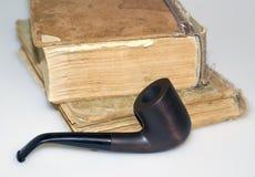 Libros gastados y tubo de tabaco Imagen de archivo libre de regalías