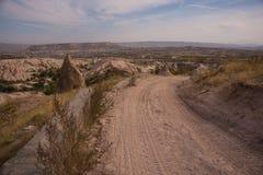 Uchisar, Cappadocia, Turquie : La route mène à la ville et à la forteresse d'Uchisar Maisons et églises de roche photographie stock libre de droits