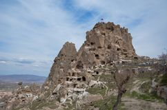 Uchisar Castle in Cappadocia Turkey, blue and cloudy sky. royalty free stock photos