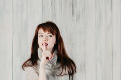 ucichnięcie Widok pyta dla ciszy, zaciszności lub sekretności z palcem na wargach uwodzicielska kobieta, patrzeje sideway Shh ręk zdjęcia stock