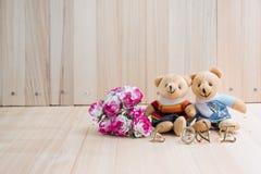 Uścisków niedźwiedzie w miłości, siedzą blisko bukieta wzrastali Obrazy Royalty Free
