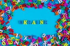 UCRÂNIA - palavra composta de letras coloridas pequenas no quadro azul do fith do fundo dos muitos letra pequena 2017 anos Imagens de Stock