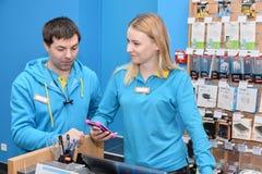 Ucrânia, Shostka - 8 de março de 2019: Suportes dos consultantes dos vendedores atrás do contador da loja fotografia de stock