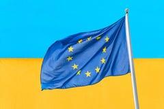 Ucr?nia e Uni?o Europeia Bandeira de ondulação da União Europeia contra a bandeira amarela azul do ucraniano da parede Ucrânia va fotografia de stock royalty free