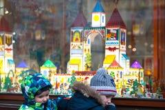 Ucrania, Lviv - 6 de diciembre de 2018 Dos niños pequeños en una calle de Lviv que mira la ventana de la tienda adornada para la  fotografía de archivo libre de regalías