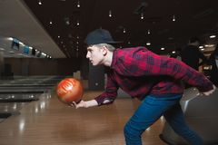 Uczeń bawić się kręgle Młody człowiek robi kręgle balonowi rzucać Rzucać kulą na śladzie Fotografia Stock
