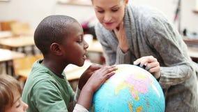 Uczeń i nauczyciel patrzeje kulę ziemską zbiory wideo