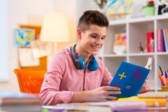 Uczeń jest ubranym słuchawki na jego szyi matematyki czytelniczej książce obraz royalty free