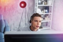 Uczeń jest ubranym słuchawki siedzi przed komputerem bawić się gry fotografia stock
