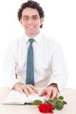 Uczeń jest ubranym szkła i krawat relaksuje z książką i wzrastał Zdjęcia Royalty Free