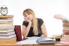 Uczeń męczył patrzeć laptop przy biurkiem w bibliotece napychającej z stertami książki Fotografia Stock