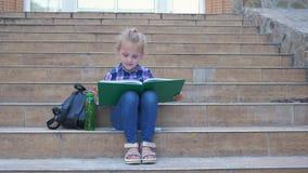 Uczeń mała dziewczynka czyta książkowego obsiadanie na krokach szkoła obok plecaka podczas przerwy