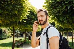 Uczeń opowiada przy telefonem komórkowym z plecakiem zdjęcie royalty free