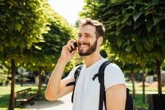 Uczeń opowiada przy telefonem komórkowym z plecakiem obraz royalty free