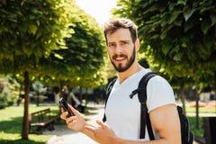Uczeń opowiada przy telefonem komórkowym z plecakiem fotografia royalty free