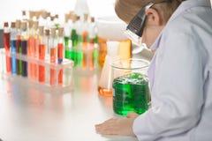 Uczeń patrzeje kolbę w lab żakiecie i ochronnych gogle z zieloną próbką Zdjęcie Stock