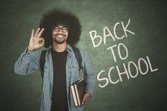 Uczeń pokazuje ok znaka z z powrotem szkoła tekst Obrazy Stock
