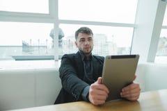 Uczeń siedzi w kawiarni i używa internet z pastylką Czujny oko w gadżecie podczas kawowej przerwy obraz royalty free