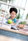 Uczeń studiuje obsiadanie przy stołem Zdjęcie Royalty Free