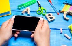Uczeń trzyma telefon komórkowego w tle kreatywnie bałagan na desktop miejsce pracy uczeń fotografia royalty free