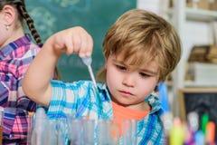 Uczeń w chemii klasie tylna szko?y poj?cie edukacyjny mały bopy naukowiec robi eksperymentom w laboratorium zdjęcia stock