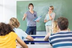 Uczeń wyjaśnia notatki oprócz nauczyciela w klasie zdjęcia stock