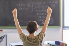 Uczeń z rękami up w sala lekcyjnej podczas lekci zdjęcia royalty free
