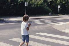 Uczeń z telefonem na zwyczajnym skrzyżowaniu iść do domu zdjęcia royalty free
