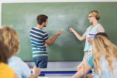 Uczeń i nauczyciel wskazuje przy blackboard Fotografia Royalty Free