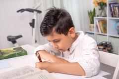 Ucze? siedzi przy sto?em w domu i robi jego pracie domowej zdjęcia stock
