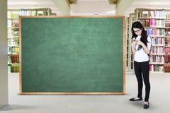 Uczeń z pustym blackboard w bibliotece Zdjęcie Royalty Free