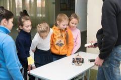 Uczennic dziewczyny są uśmiechnięte i patrzeć domowej roboty samochodu modela obraz stock