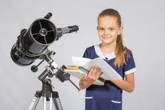 Uczennica astronom leafing przez książek stoi przy teleskopem Fotografia Stock