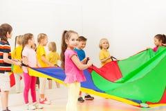 Uczennica bawić się spadochron z przyjaciółmi w gym fotografia royalty free