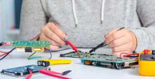 Uczennica naprawia elektroniczną drukowaną obwód deskę adaptatoru komputerowej grafiki odizolowywający remontowy śrubokrętu biel Fotografia Royalty Free