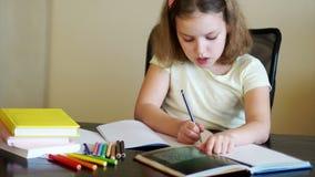 Uczennica robi pracie domowej Na stole są podręczniki, ćwiczeń ołówki, książki, i tylna szkoły przygotowanie zbiory wideo