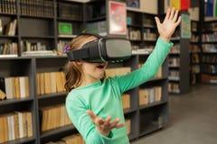 Uczennica używa rzeczywistości wirtualnej słuchawki w bibliotece obraz stock