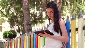 Uczennica używa pastylka komputer osobistego przed szkołą zbiory
