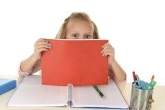 Uczennica z blondynu uśmiechniętym szczęśliwym obsiadaniem na biurku figlarnie podczas gdy robić pracie domowej Fotografia Stock
