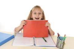 Uczennica z blondynu uśmiechniętym szczęśliwym obsiadaniem na biurku figlarnie podczas gdy robić pracie domowej Zdjęcie Royalty Free