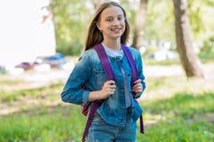Uczennicy dziewczyna jest uśmiechnięta w lecie w parku Za plecakiem Pojęcie z powrotem szkoła Emocje szczęście i zdjęcie royalty free
