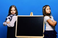 Uczennicy obok chalkboard odizolowywającego na błękitnym tle obraz stock