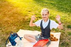 Uczennicy ono uśmiecha się i pokazuje radosny ok znak uczeń siedzi w parku na koc z miękkiej części zabawki zabawkami niedźwiedź  obrazy stock