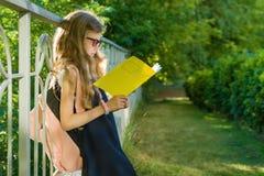 Uczennicy szkoły podstawowej uczeń jest ubranym szkła z plecakiem czyta szkolnego notatnika, stoi blisko ogrodzenia, w boisku szk Fotografia Stock